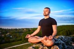 人的画象坐在莲花坐的一个岩石反对蓝天 免版税库存图片