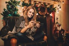 年轻人的画象集中了comething在圣诞节前的妇女读书 库存照片