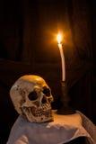 人的头骨和灼烧的蜡烛 库存图片