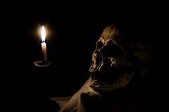 人的头骨和灼烧的蜡烛 免版税图库摄影