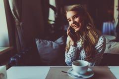 年轻人相当女性充满好心情谈话在有她的朋友的流动巧妙的电话,当放松在咖啡馆时 免版税图库摄影