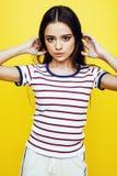 年轻人相当少年妇女情感摆在黄色背景,时尚生活方式人概念 图库摄影