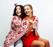 年轻人相当愉快微笑白肤金发和深色的妇女女朋友在圣诞老人红色帽子的圣诞节和假日装饰 免版税库存照片
