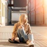 年轻人相当时兴的白肤金发的妇女在被剥去的牛仔裤穿戴了 图库摄影