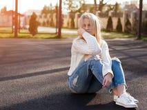 年轻人相当时兴的白肤金发的妇女在被剥去的牛仔裤穿戴了 库存照片