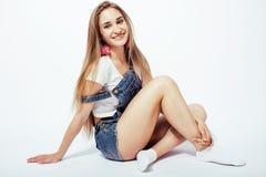 年轻人相当白肤金发十几岁的女孩情感摆在,在白色背景隔绝的愉快微笑,生活方式人概念 库存图片