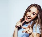 年轻人相当白肤金发十几岁的女孩情感摆在,在白色背景隔绝的愉快微笑,生活方式人概念 免版税库存照片
