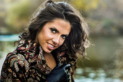 年轻人相当美丽的妇女室外画象摆在有湖的秋天公园的背景的 免版税图库摄影