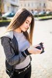 年轻人相当滑稽的肉欲的妇女摄影师旅游女孩摆在室外与照片照相机 图库摄影