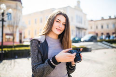 年轻人相当滑稽的肉欲的妇女摄影师旅游女孩摆在室外与照片照相机 库存图片
