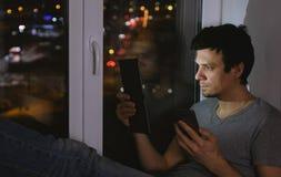 人看片剂和手机 坐在黑暗的窗台 库存图片