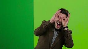 人看从绿色委员会的后面,做鬼脸和皮 绿色屏幕 慢的行动 股票视频
