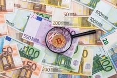 人看bitcoin通过放大镜反对 免版税库存图片
