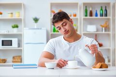 人睡着在他的早餐期间在超时工作以后 库存图片