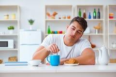 人睡着在他的早餐期间在超时工作以后 免版税库存图片