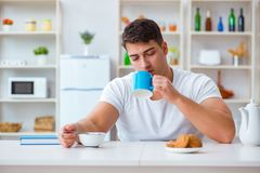 人睡着在他的早餐期间在超时工作以后 库存照片