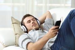 人睡觉听的音乐在家 免版税库存图片