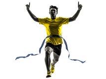 年轻人短跑选手赛跑者连续优胜者终点线剪影 免版税图库摄影