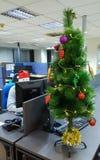 人研究计算机在办公室在圣诞树附近 免版税库存照片