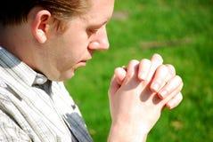 人祈祷的年轻人 库存照片