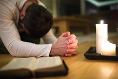 年轻人祈祷,下跪,圣经和蜡烛在他旁边 免版税库存照片
