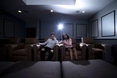 人种间夫妇在一个家庭影院日期 免版税图库摄影
