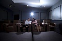 人种间夫妇在一个家庭影院日期 免版税库存照片