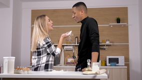 人种间夫妇在厨房里饮用乐趣投掷的面粉在彼此 股票视频