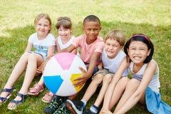人种间小组孩子在夏天 免版税库存图片