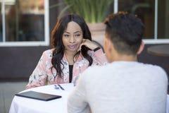 人种间由别人安排的男女初次会面在室外餐馆 库存照片
