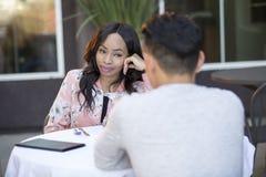 人种间由别人安排的男女初次会面在室外餐馆 免版税库存图片