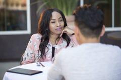 人种间由别人安排的男女初次会面在室外餐馆 免版税图库摄影