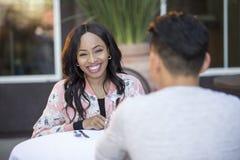 人种间由别人安排的男女初次会面在室外餐馆 免版税库存照片