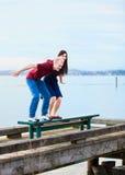 年轻人种间夫妇一起坐在湖的船坞 免版税库存图片