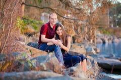 年轻人种间夫妇一起坐岩石海岸线  免版税库存照片