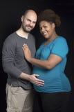 年轻人种间夫妇爱抚的母亲的腹部 免版税库存图片