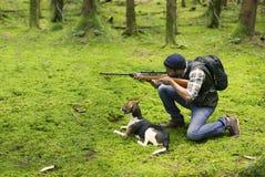 人种间猎人在瞄准牺牲者的森林里 免版税库存图片