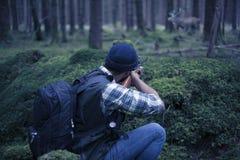 人种间猎人在瞄准牺牲者的森林里 库存照片