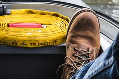 人穿坚韧靴子和牛仔裤的` s脚在有a的一艘船上 免版税库存图片