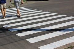 人穿过路在一条行人交叉路 免版税库存图片