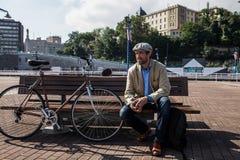 人穿戴的偶然坐在自行车旁边 免版税库存图片