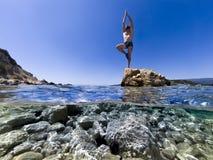 人立场在一只脚的一个岩石平衡了 图库摄影