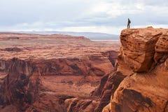 人站立在山顶部 有站立在岩石的背包的远足者,享受谷视图,亚利桑那 库存图片