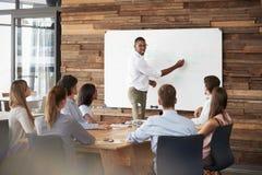 年轻黑人站立在whiteboard对队演讲在会议上 免版税库存照片