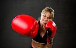 年轻人符合和红色拳击手套与在健身房feeli的坚强的可爱的拳击手女孩投掷的积极的拳打训练锻炼战斗 免版税库存图片