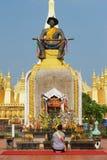 人给予一个条件为国王在Luang stupa在万象,老挝的Pha前面的晁Anouvong的雕象 图库摄影