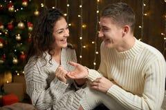 人给女孩一个定婚戒指、夫妇在圣诞灯和装饰,穿戴在白色,杉树在黑暗的木ba 免版税库存图片
