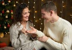 人给女孩一个定婚戒指、夫妇在圣诞灯和装饰,穿戴在白色,杉树在黑暗的木ba 免版税库存照片