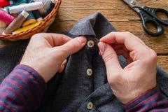 人缝合按钮到他的衬衣 免版税库存图片