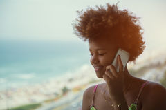 年轻黑人美丽的卷曲女孩说在电话里在海滩附近 库存图片
